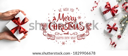 Merry Christmas and New Year text on white background with gift boxes, red decoration, bokeh, sparkles and confetti. Xmas greeting card. Female hands holding Christmas gift box. Flat lay, top view Royalty-Free Stock Photo #1829906678