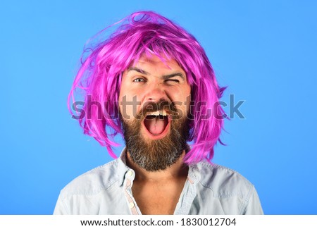 Funny bearded man in wig. Handsome bearded man with mustache in wig. Fashion concept. Barbershop. Hipster in periwig. Happy stylish man with pink hair. Royalty-Free Stock Photo #1830012704