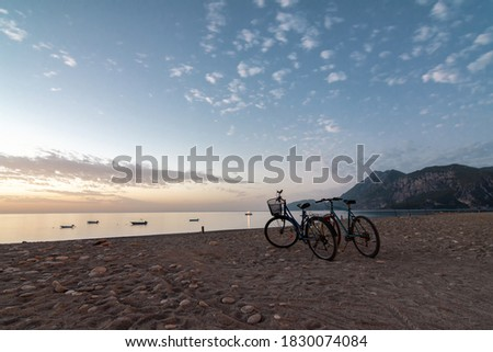 Morning on the beach in the village of Cirali, bicycles stand on the beach. Boats and ships in the distance of the Taurus mountain are moored near the shore. Landscapes of the Lycian Trail. Royalty-Free Stock Photo #1830074084