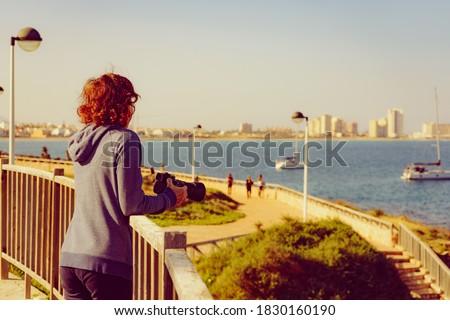 Tourist woman visit Cape Palos, Cartagen Murcia region, Spain. Female taking travel picture with professional camera, enjoy La Manga sea view.