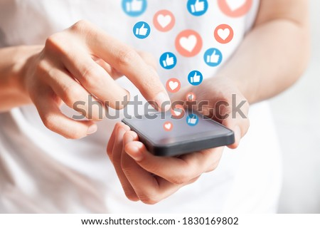 Person interacting on social media network with smartphone by liking and loving posts. Advertising on mobile phone by collecting user data and targeting profiles Royalty-Free Stock Photo #1830169802
