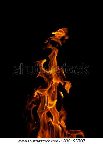 Close-up vertical picture of an isolated bright and hot yellow flame with numerous of tongues on the black background