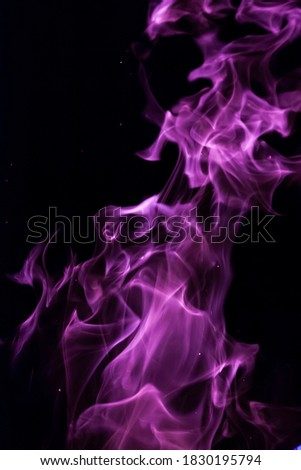 Close-up vertical picture of an isolated bright purple flame with numerous of tongues on the black background