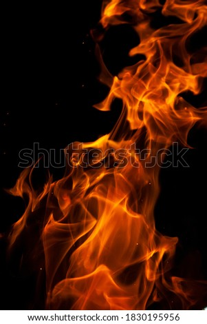 Close-up vertical picture of an isolated bright and hot golden flame with numerous of tongues on the black background