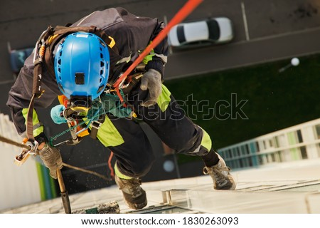 Industrial mountaineering worker hangs over residential building while washing exterior facade glazing. Rope access laborer hangs on wall of house. Concept of urban works. Copy space Royalty-Free Stock Photo #1830263093