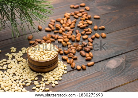 Pine nut kernels in wooden box. Pine nuts on table. green cedar branch. Dark wooden background. View from above Royalty-Free Stock Photo #1830275693
