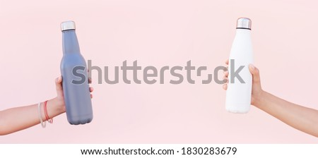 Close-up of women hands holding eco reusable steel stainless thermo water bottles of white and blue colors, on the background of pastel pink color.