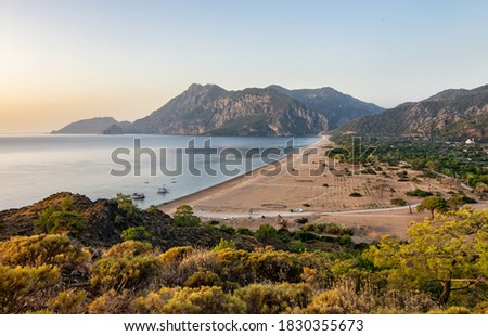 Morning on the beach in the village of Cirali. Boats and ships in the distance of the Taurus mountain are moored near the shore. Landscapes of the Lycian Trail. Royalty-Free Stock Photo #1830355673