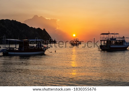Morning on the beach in the village of Cirali. Boats and ships in the distance of the Taurus mountain are moored near the shore. Landscapes of the Lycian Trail. Royalty-Free Stock Photo #1830355676