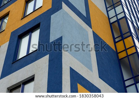 Element of the facade of a modern European building. The facade is painted with multi-colored geometric shapes Royalty-Free Stock Photo #1830358043