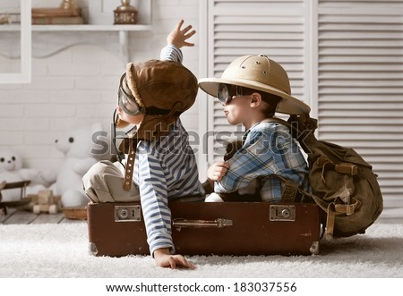 Two boys in the form of an aircraft pilot and traveler playing in her room Royalty-Free Stock Photo #183037556