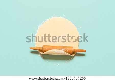 Home baking concept with raw dough rolled out with a rolling pin, isolated on a green-mint background. Top view of homemade pie crust on the table. #1830404255