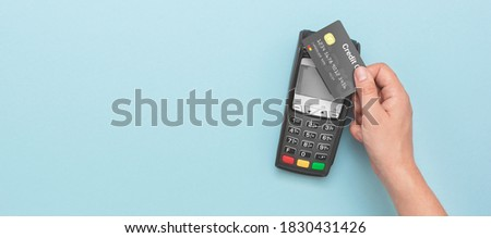 Credit card payment terminal. Man using credit card. Wide image with copy space and blue background Royalty-Free Stock Photo #1830431426