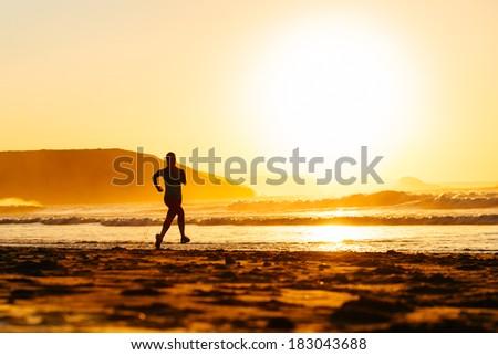 Woman athlete silhouette running on beautiful orange summer sunset or morning at the beach. Fitness runner lifestyle scene. #183043688
