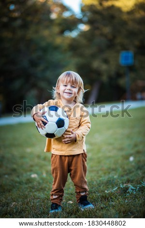 Little foot ballplayer. Little boy with football ball on grass.  Royalty-Free Stock Photo #1830448802