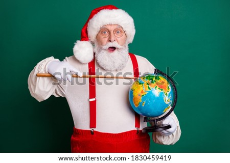 Portrait of his he handsome cheerful amazed clever fat bearded Santa professional teacher holding in hands globe showing country continent map planet science lesson isolated green color background #1830459419