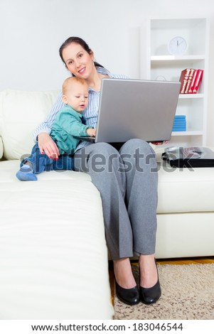 Young business woman with laptop and her baby boy #183046544