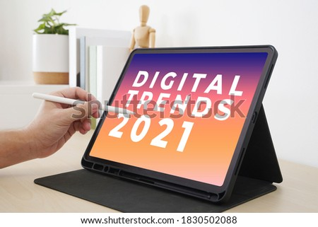 Digital Trends 2021 on tablet screen with hand holding interactive pen, Digital marketing, Business and technology concept. Royalty-Free Stock Photo #1830502088