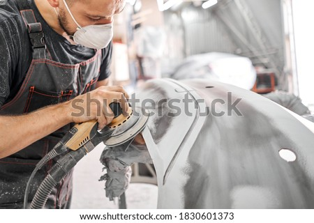 The mechanic works with a grinding tool. Sanding of car elements. Garage painting car service. Repairing car section after the accident. Royalty-Free Stock Photo #1830601373