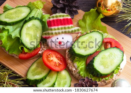 Christmas snacks, vegetarian sandwiches with vegetables and cheese. Children's menu, funny food, face, snowman. New year's food