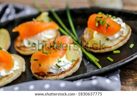 blinis with smokek salmon whipped lemon cream and chive Royalty-Free Stock Photo #1830637775