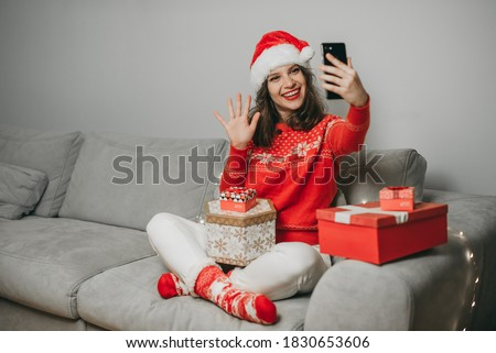 Portrait of young beautiful European woman in a Christmas hat, red knitted sweater with holiday gifts sitting, chatting smartphone at home, quarantine coronavirus. new year gifts, girlfriend, hi Royalty-Free Stock Photo #1830653606