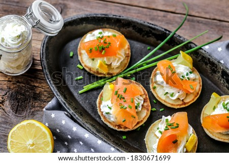 blinis with smokek salmon whipped lemon cream and chive Royalty-Free Stock Photo #1830671699