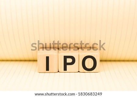 Wooden blocks with the word IPO Initial public offering, stock market launch . Business and finance concept top view, scattered cubes around random letters