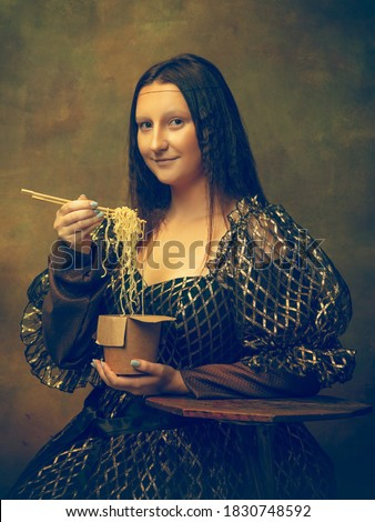 Instant noodles. Young woman as Mona Lisa, La Gioconda isolated on dark green background. Retro style, comparison of eras concept. Beautiful female model like classic historical character, old Royalty-Free Stock Photo #1830748592