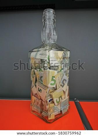 5 Euro Scheine gefaltet in einer Jack Daniels Flasche