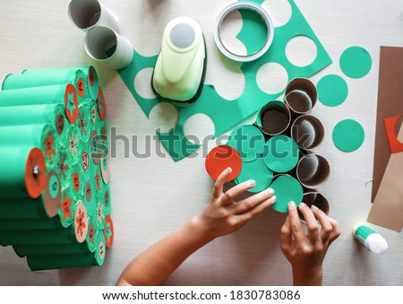 Cute little kid making handmade advent calendar with toilet paper rolls at home. Glue, colored paper, cut punch to hide sweets and candies in rolls. Seasonal activity for kids, family winter holidays #1830783086
