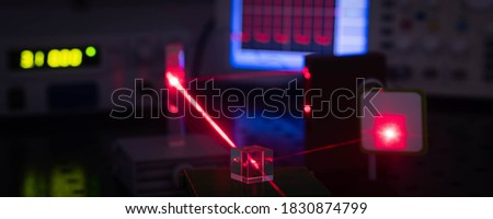 Experiment in optic lab with laser device. Red laser on optical table in physics laboratory #1830874799