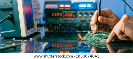 Debugging electronics device. PCB witch microcontroller in electronics laboratory Royalty-Free Stock Photo #1830874841