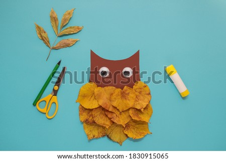 "dry leaves applique art autumn. little child making autumn decoration ""Owl"" from leaves. Children's art project. DIY concept. Step-by-step photo instruction. Step 4"