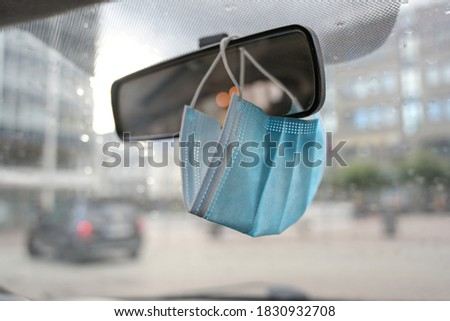 Surgical face mask as protection against covid-19 infection is hanging in a car on the rear view mirror during the coronavirus pandemic, copy space, selected focus, narrow depth of field Royalty-Free Stock Photo #1830932708