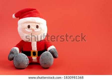 Plush santa claus. Christmas soft toy on a red background. Plush santa. Christmas concept. New Year's toys. Christmas.
