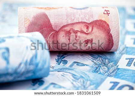 100 reais banknote and one hundred yuan banknote, Chinese leader, detail of a renminbi banknote and a Brazilian banknote. Concept of negotiation between china and brazil #1831061509
