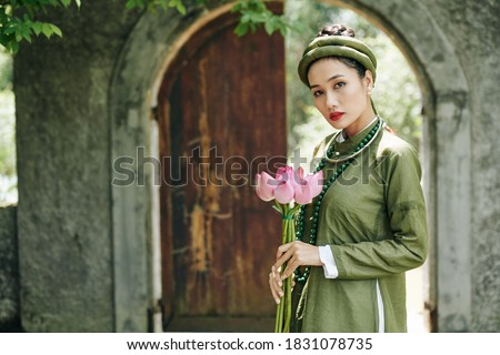 Portrait of attractive serious young woman in traditional Vietnamese dress and headwear holding lotus flowers and looking at camera Royalty-Free Stock Photo #1831078735