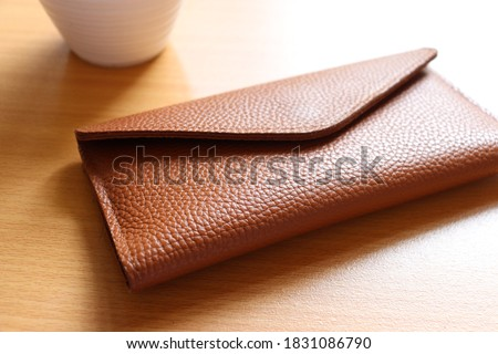 leather wallet on wood texture Royalty-Free Stock Photo #1831086790
