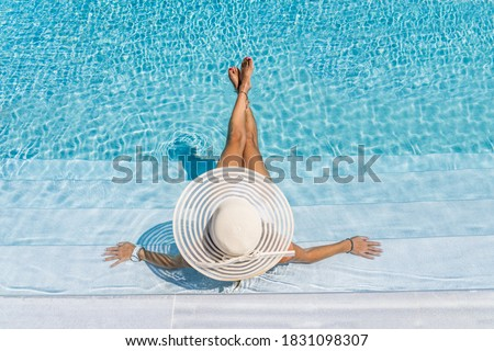 woman in luxury five stars  spa resort in the swimming pool.  Royalty-Free Stock Photo #1831098307