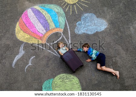 Happy little toddler girl and kid boy flying in hot air balloon painted with colorful chalks in rainbow colors on ground or asphalt in summer. Two children, siblings having fun. Creative leisure