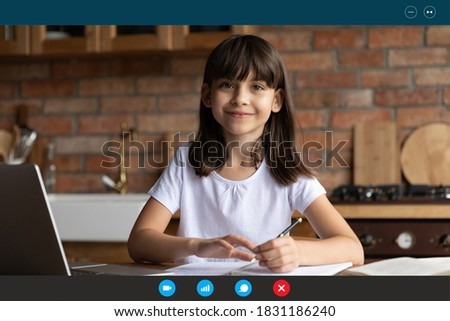 Screen view of smiling small girl child sit at desk in home kitchen study online on computer. Happy little kid talk speak on video call, have webcam lesson with teacher. Distant education concept.