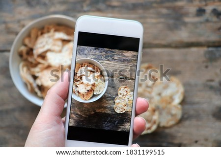 Woman takes picture of brown rice chips with chia and quinoa seeds