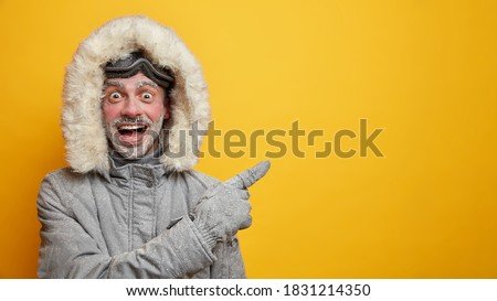 Happy frozen man in warm clothes has fun during winter points away on empty space wears gloves isolated on yellow background. Cheerful male adventurer with frosted beard and ski goggles has expedition #1831214350