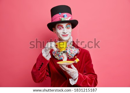 Crazy hatter with professional vivid colorful halloween makeup dressed in costume poses with cup of tea against pink studio background. Gorgeous male character prepares for carnival party. Face art
