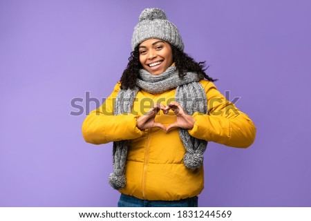 I Love Winter. Cheerful Black Woman Gesturing Heart Shape Smiling To Camera Posing Over Purple Studio Background, Wearing Warm Clothes. Love, Romance, Happy Winter Season Concept