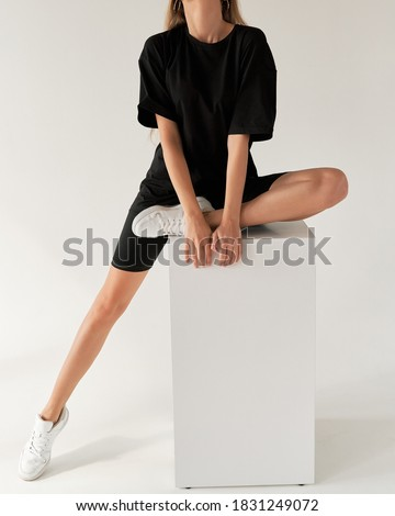 woman wears oversize black shirt and black shirt. dark streetwear outfit young girl Royalty-Free Stock Photo #1831249072