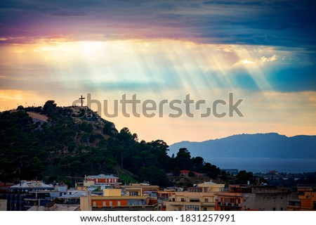 Beam of light through the clouds over a cross on top of the hill. Rays of light shining through clouds. Celestial entity over a hill with a crucifix that protects the city. Cross silhouette. Royalty-Free Stock Photo #1831257991
