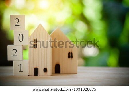 Two wooden houses model with wooden block number 2021 concept to show new house, new year property, property concept isolated on green bokeh background.