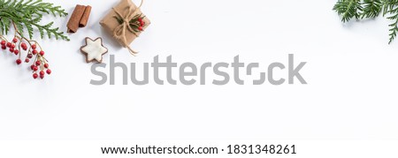 Oblong Christmas banner with small, wrapped gifts and other xmas decorations like spruce and fir twigs isolated on white background and lots of space for text. Royalty-Free Stock Photo #1831348261